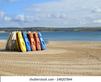Several Multi-Coloured Canoes On The Beach