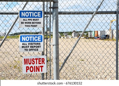 Several notice signs hanging on a chain link fence.