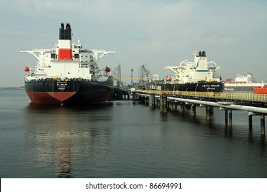 Several oil tankers bringing their cargo in a tank storage facility in Rotterdam harbour.