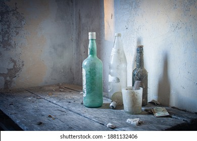 Several old and dirty bottles on old table and casting their shadow on the wall of an abandoned house.