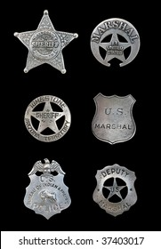Several old, vintage sheriff, marshall, and police badges isolated over black
