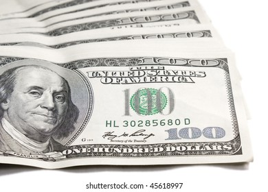 Several one hundred dollar bills spread on white background