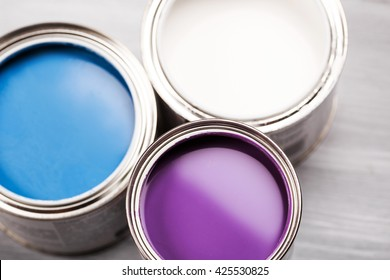 Several opened cans with paint inside. Blue, lavender or violette and white. Close up.