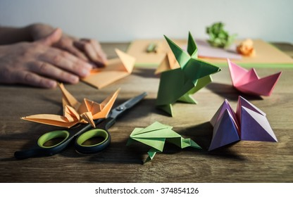 Several origami figures on a wooden table - in the background hands folding colored paper.
