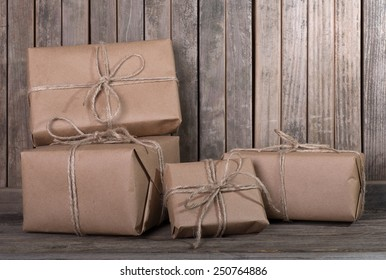 Several packages wrapped in plain brown paper and tied with string on a rustic wood background with copy space