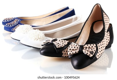 several pairs of female flat shoes isolated on white