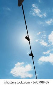 Several pairs of sneakers hanging on a rope against the blue sky. One of the shoes covers the sun.