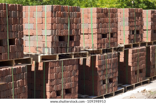 several pallets of red brick pavers waiting to be installed