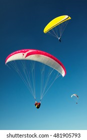 Several paragliders flies over a hillside on a background of blue sky.