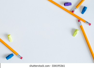 Several pencils and erasers placed in a pleasing way on white paper to create a border for multiple purposes. This can be used as a horizontal or vertical format or it can even be flipped and rotated.
