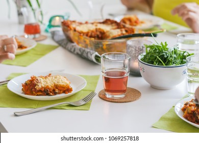 Several people dine at the table have lasagna cooked at home.