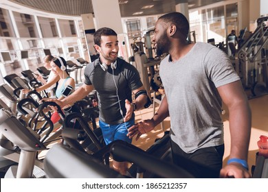 Several people are engaged on the treadmills in the modern gym. Athletes are focused on running. Behind them, modern fitness equipment for sports.