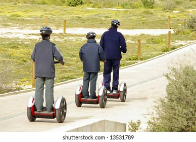 Several people moving over a modern omnidirectional personal transport platform (segway)