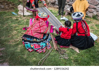 Several Peruvian women weaving a long striped textile on the ground