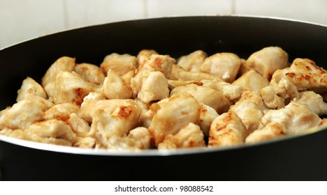 several pieces of chopped up chicken breast browned in a frying pan