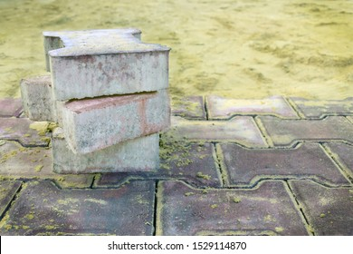 several pieces of paving slabs lie in the place of repair of the sidewalk, road, square, on the background of sand. laying of paving slabs. paving slab production advertisement