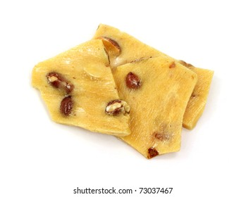 Several pieces of peanut brittle on a white background.