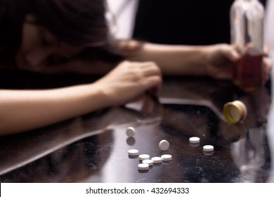 Several pill spilled on table Near bottle of alcohol.