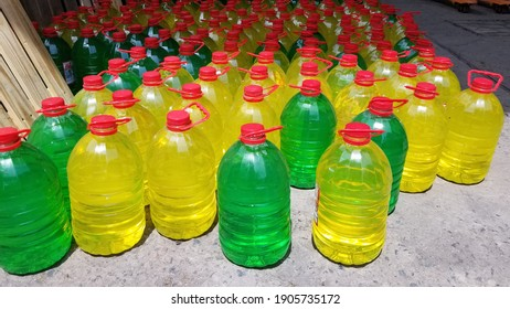 Several plastic gallons with red lid. many plastic gallons of colored liquid. plastic gallons with soap, with shampoo. wholesale gallon warehouse