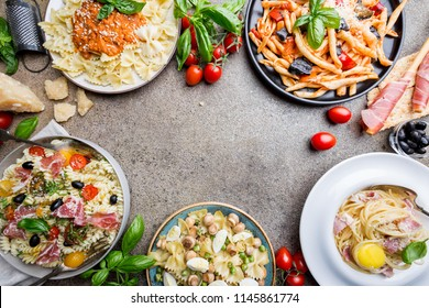 Several plates of pasta with different kinds of sauce over stone background, top view. Concepts of Italian food.