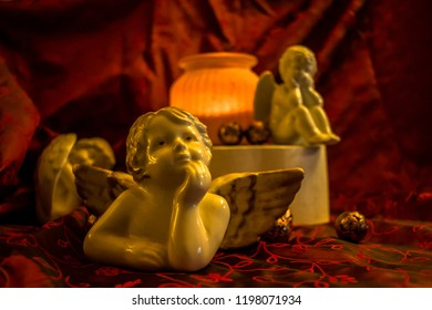 Several porcelain angels and a burning lantern on a red festive cloth. Suitable for Christmas or a bereavement. Selected focus and narrow depth of field