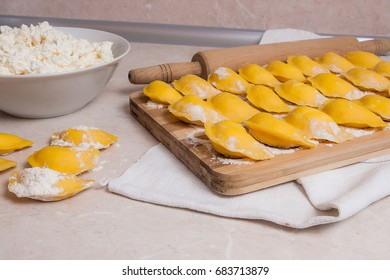Several ready for boiling vareniki, dumplings, pierogi with cottage cheese or curd on wooden cutting board with flour. Fresh prepared yellow rolled out dough with white flour and cottage cheese