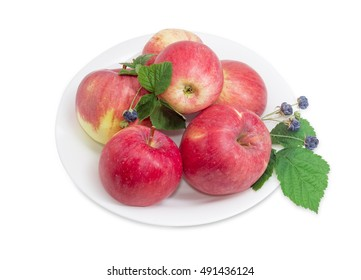 Several red apples and twigs of blackberry with berries and leaves on the white dish on a light background