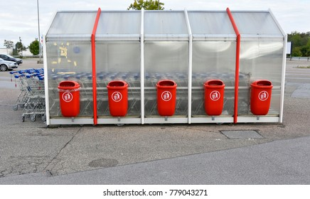 Several red rubbish bins in a parking lot