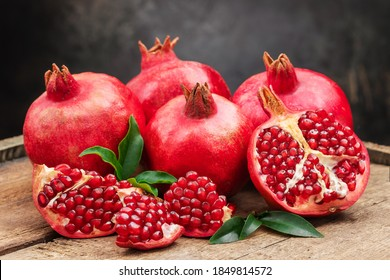 Several ripe pomegranate fruits and an open pomegranate with pomegranate leaves on a wooden old cutting board, side view, dark background.
