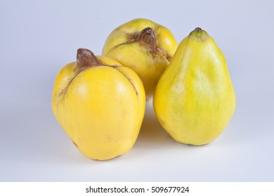 Several ripe quinces against bright background.