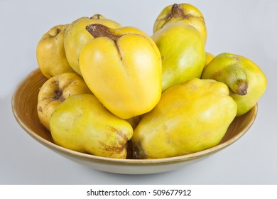 Several ripe quinces in a bowl against bright background.