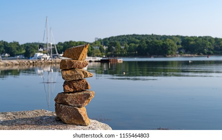 Several rocks stacked atop a large stone with a view of the harbor at Belfast Maine with the breakwater built of granite in the early morning light.