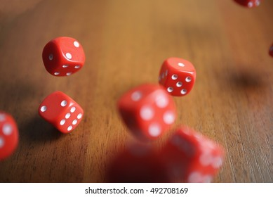 Several rolling red dice fall on a table