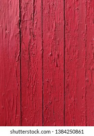 Several rough boards painted a bright red in the early morning light.