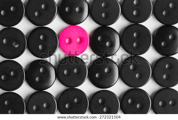 several rows of black buttons on a white background, among them the one bright pink, stands out concept, to be bright, life style