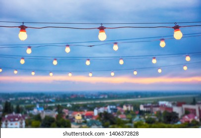 several rows of decorative outdoor light strings hanging on cityscape background at twilight