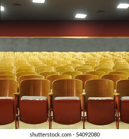 Several rows of theater seats in an auditorium with lights above.