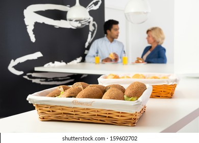 Several sandwiches on a counter, with two coworkers talking in the background