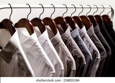 Several shirts on a hanger	 from white to black color range