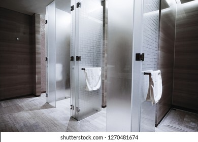 several showers seperated with walls of glass and wall and floor with dark tiles