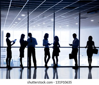 Several  silhouettes of businesspeople interacting  background business center