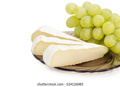Several slices of brie cheese and cluster of a white table grapes on a glass dish closeup on a light background