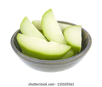 Several slices of fresh chayote squash in on old stoneware bowl on a white background.