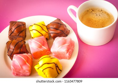 Several small cakes (french fancies) with icing in different colours on a white and a cup of coffee