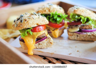 Several small cheeseburger sliders made from worm burger patties. The insect burgers are made from buffalo worms, which are the larvae of the darkling beetle.