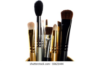 several small makeup brushes in a container