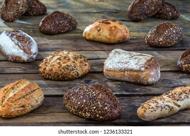 Several small multi grain  bread sprinkled with whole sunflower seeds, flax and sesame seeds and wheat and barley spikes.