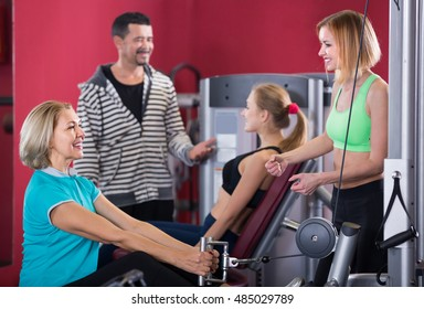 Several smiling women and man having workout on machines in gym. Focus on woman