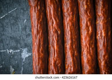 Several smoked sausages on a blue metallic background horizontal