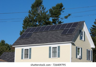 Several solar panels on the rooftop of a rural house.